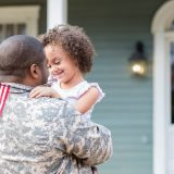 Soldier with kid in front of house