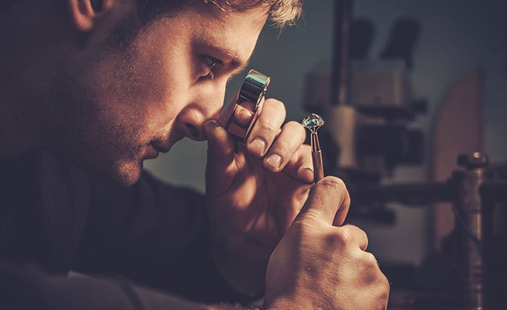 man using a spyglass and looking at a diamond