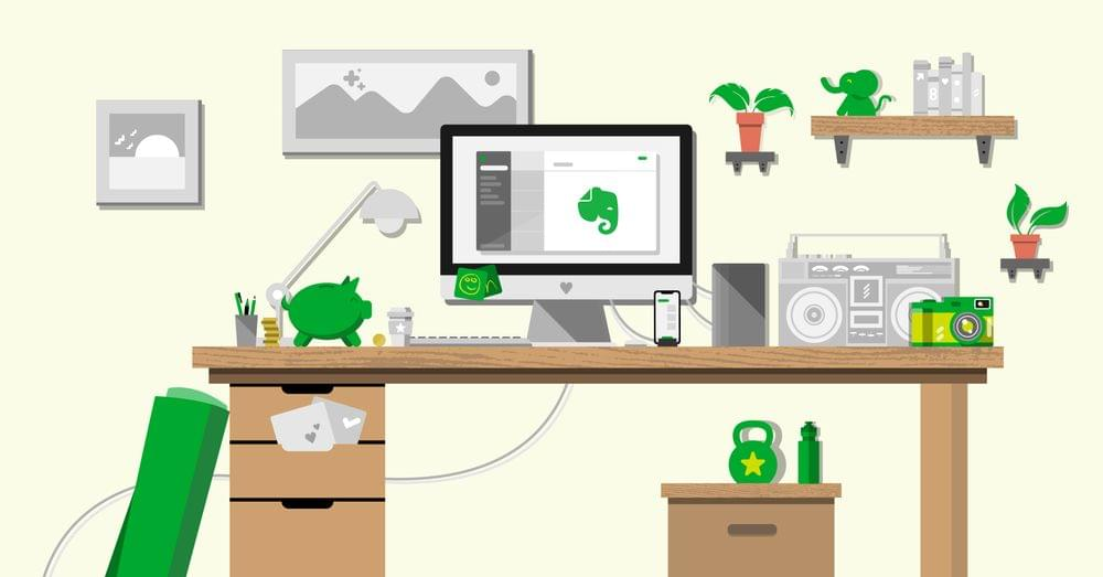 A desk with a computer showing the Evernote app