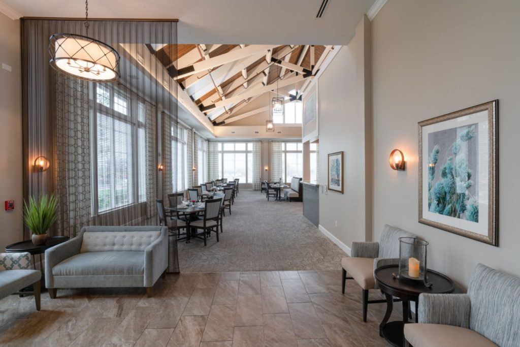 A wide hallway with modern, comfortable lounge furniture at The Culpeper senior living community in Virginia
