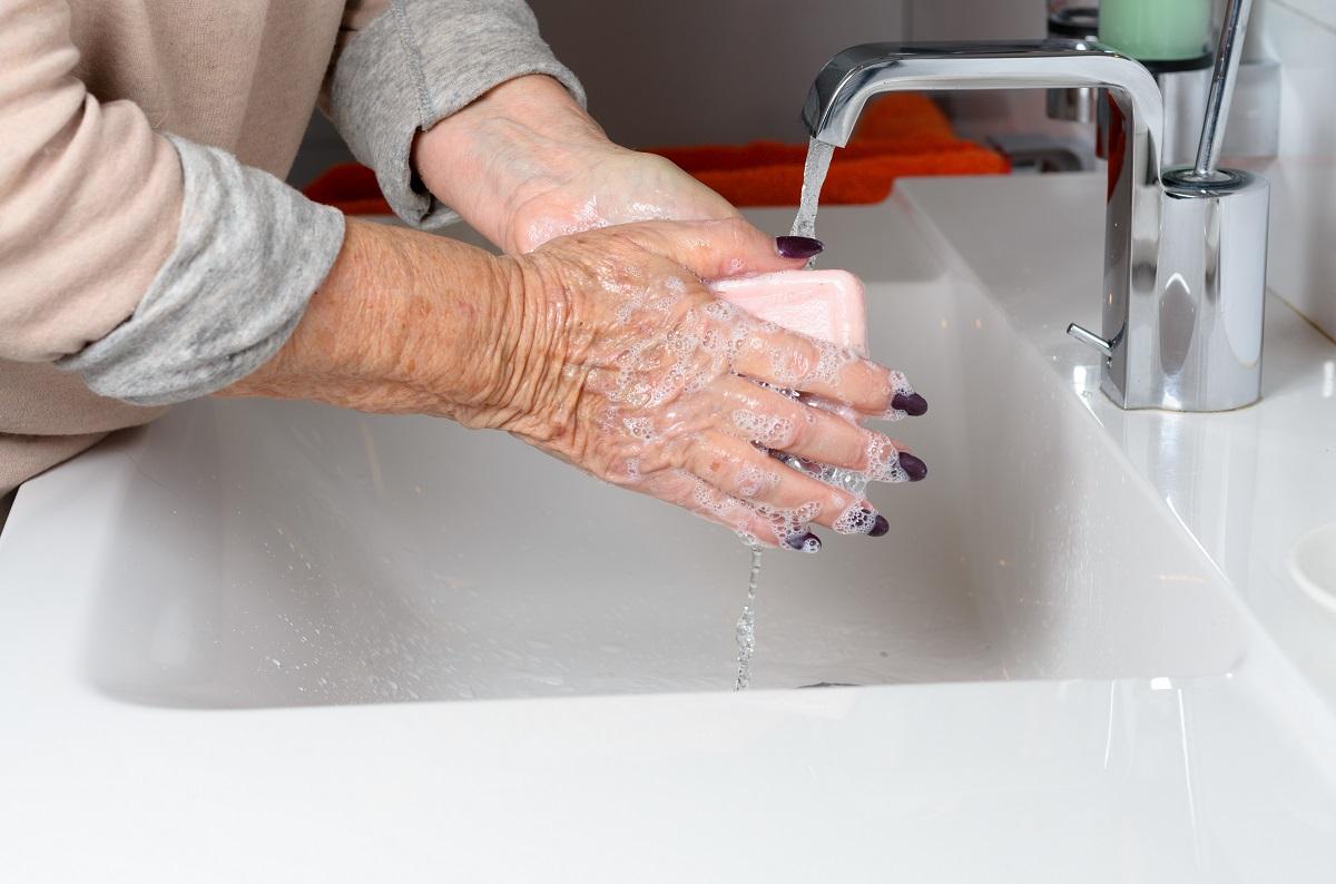 Elderly woman washing hands under tap