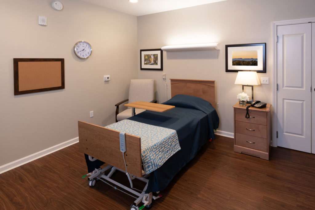 A private room in The Culpeper senior living community with a bed, chair, TV, and clock