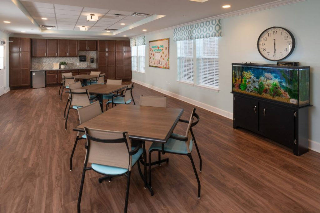 The sitting room with a clock and a fish tank at The Culpeper senior living