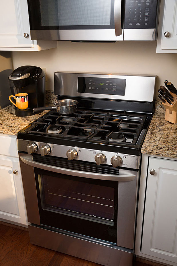 A photo of the stove and kitchen in a senior apartment cottage