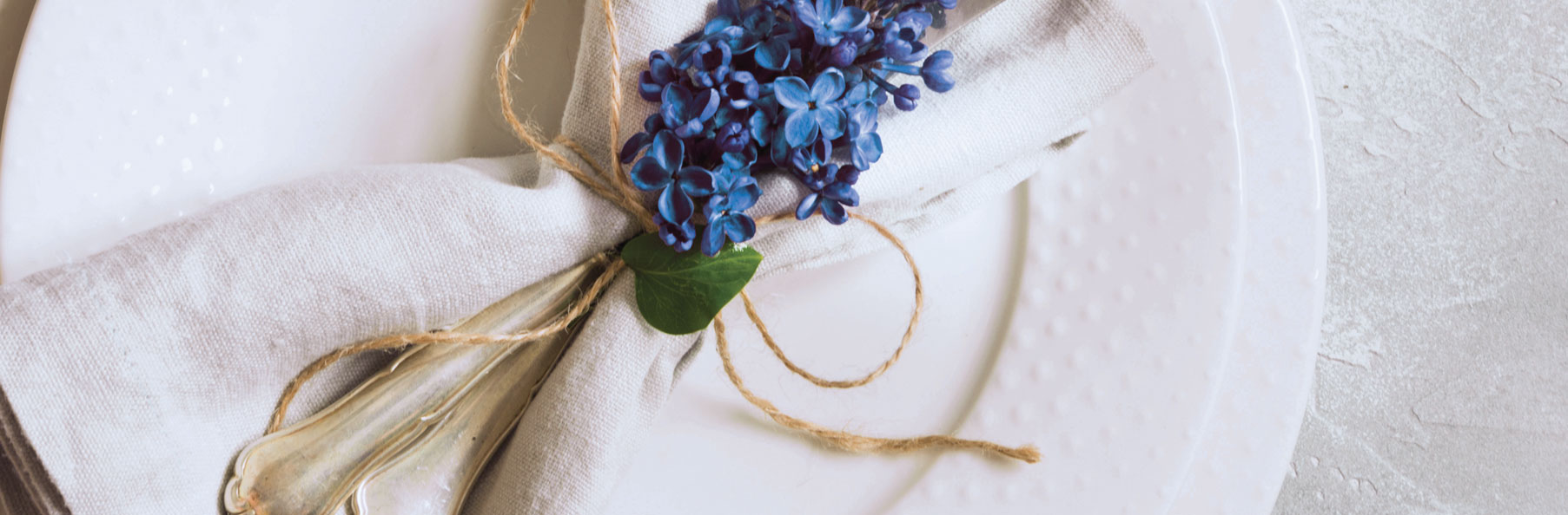 A close up photo of a plate with silverware napkin and flower