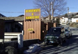 Un'insegna luminosa di 'Benvenuto a Sampeyre' in posizione strategica
