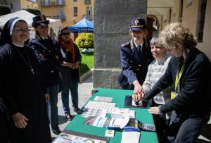 Nel giorno della cittadinanza onoraria la Polizia consegna una cartolina ricordo a un'anziana del Cottolengo