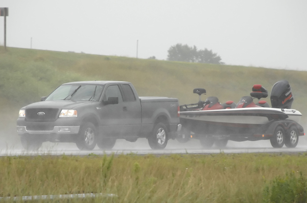 Truck towing boat trailer through rain with CURT custom wiring