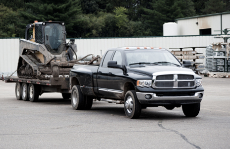 Ram truck with class 5 hitch towing large flatbed trailer and skid steer