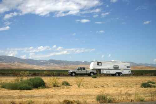Truck towing 5th wheel camper through open plains