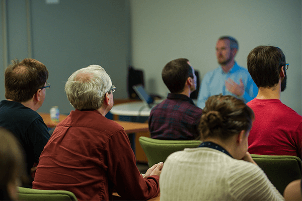 A group of people listen to a presentation.