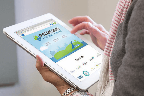 A woman uses the PyCon website on a tablet.