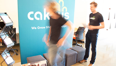 Two team members busily preparing materials for the Caktus booth
