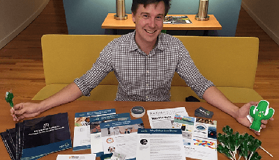 Account Manager Tim Scales with a table full of various Caktus promotional materials.