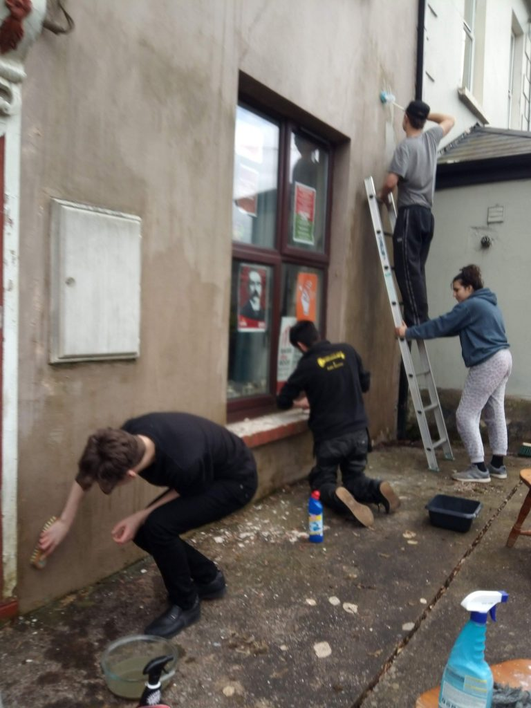 Members of the CYM cleaning the front of Connolly Barracks, preparing for a repaint
