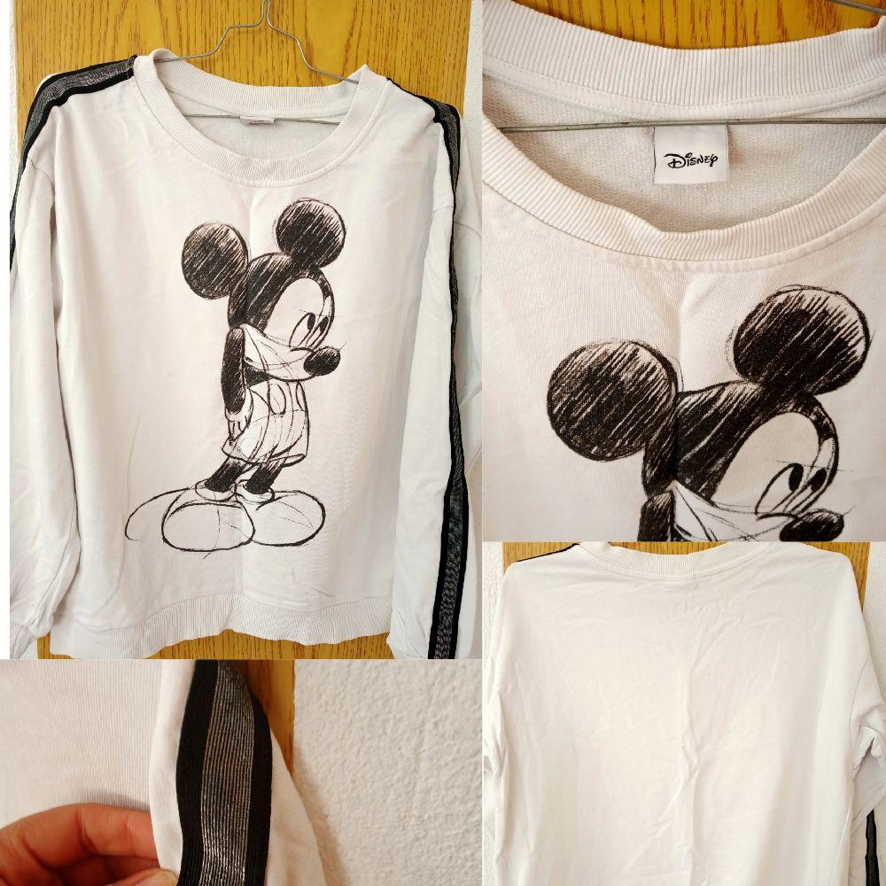 Pull sport couleur blanc avec une bande noire et argent au niveau des manches fe de la marque Disney