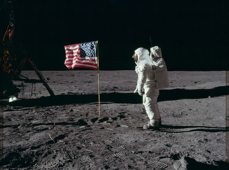 A man on the Moon stands in front of an American flag