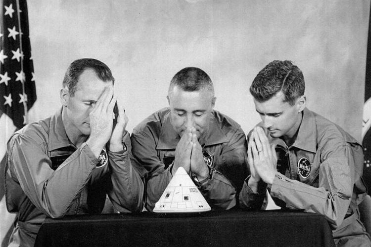 Apollo 1 crew pretending to pray over a model of their spacecraft