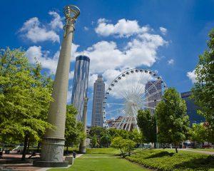 Centennial park showing pillars and a ferris wheel inside a giant green park