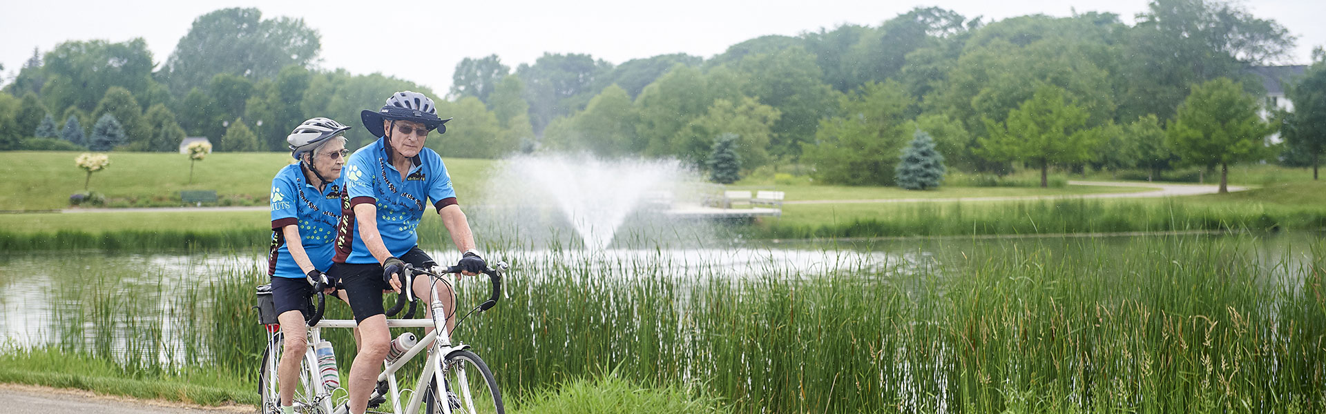 An elderly couple riding a bike around a lake at their Des Moines senior living community