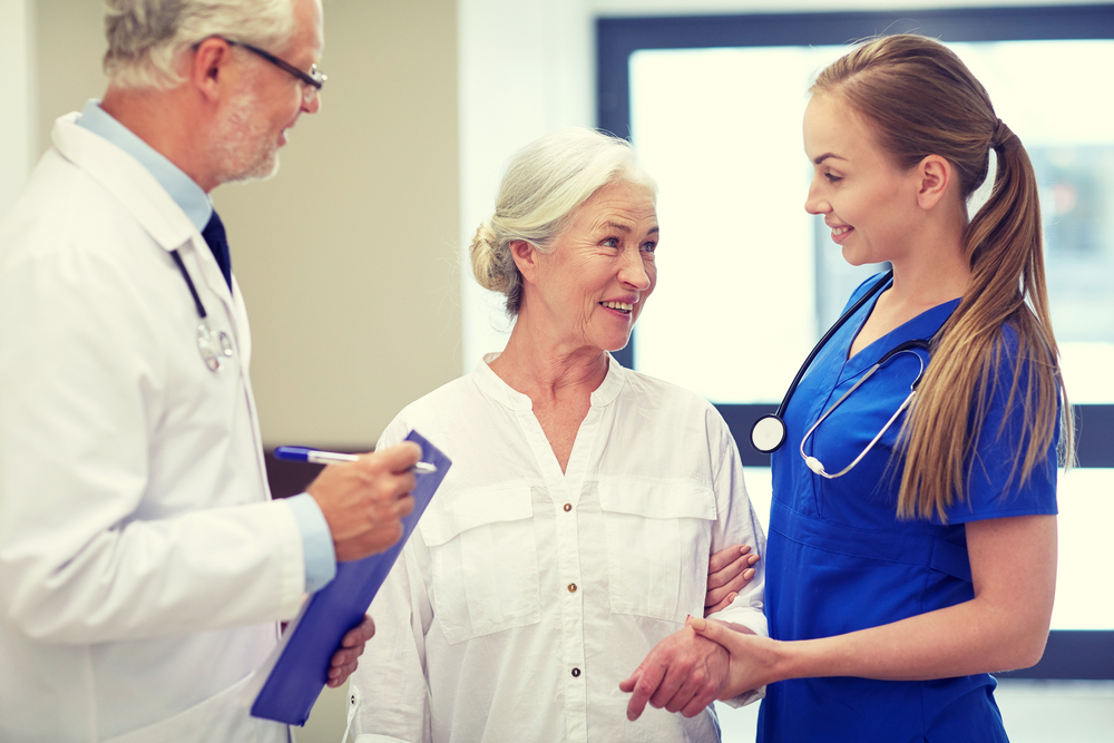 Senior woman talking with nurse and doctor