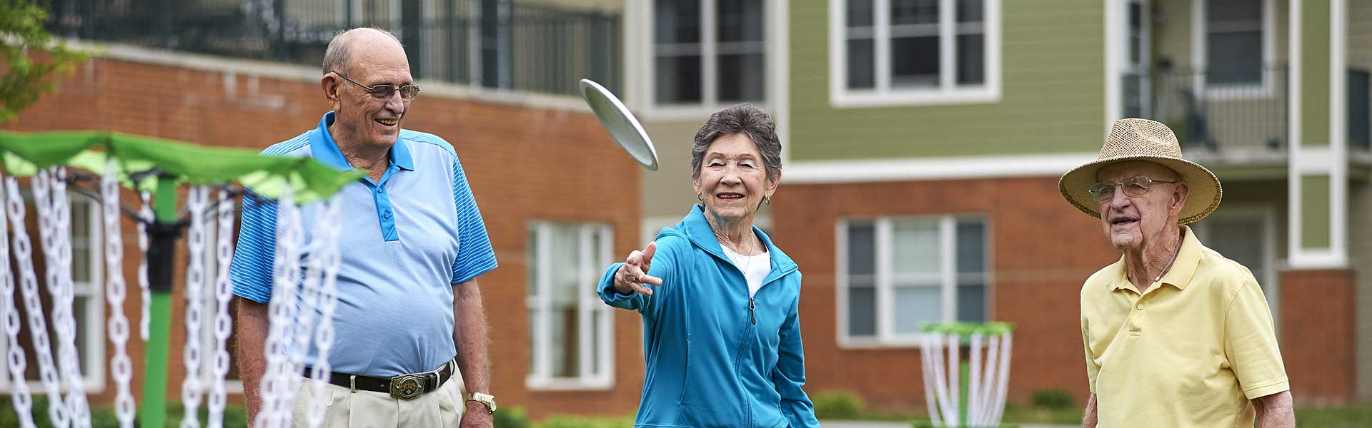 Two older men and an older woman playing disc golf at their Des Moines senior living community