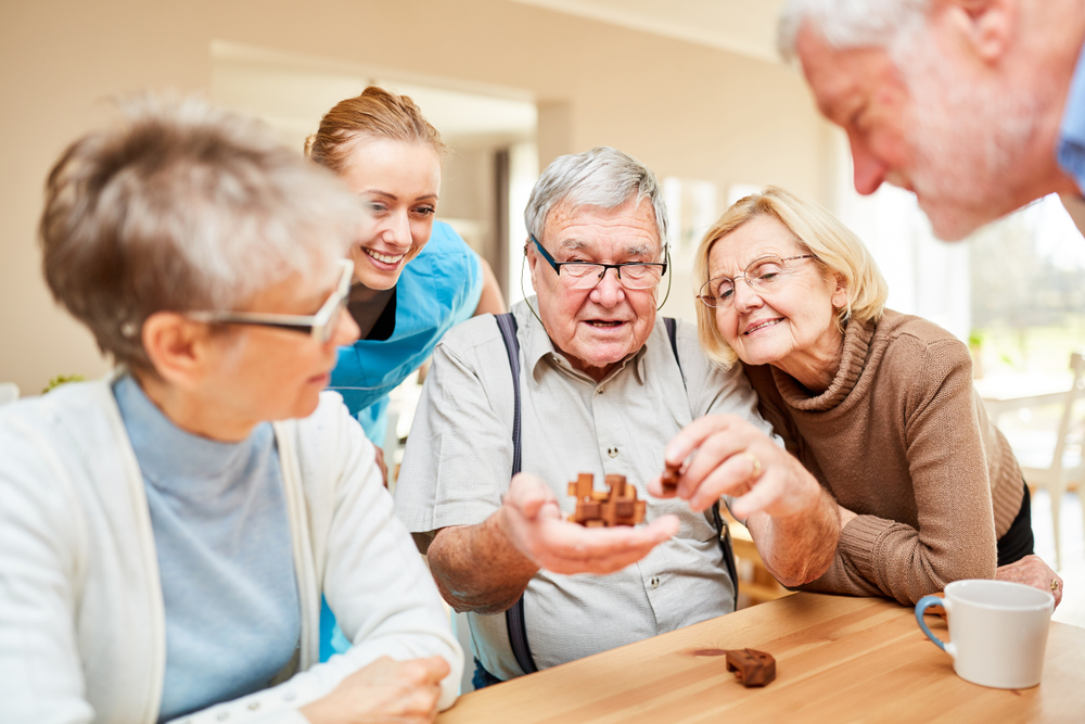 Seniors gathering around a table playing games
