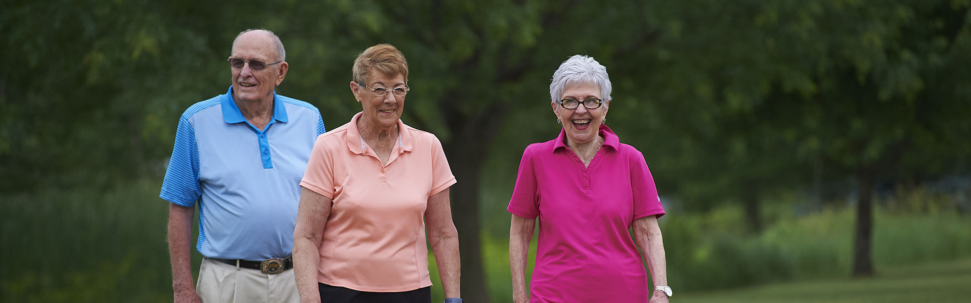 Two elderly women and an elderly man walking on an outdoor trail at their Des Moines independent living community