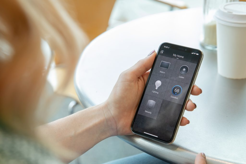 Control4 mobile app shown on iPhone held by a woman