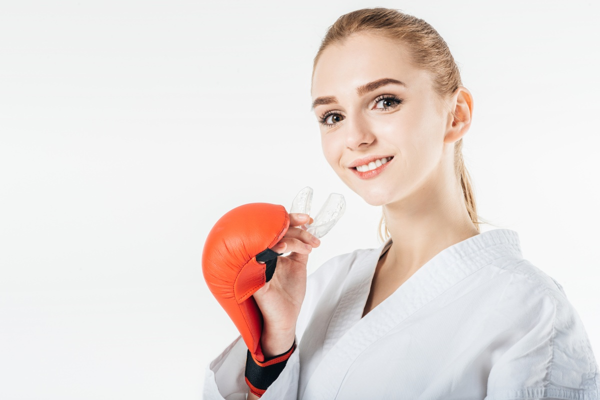 Kickboxer woman poses with sports mouth guard