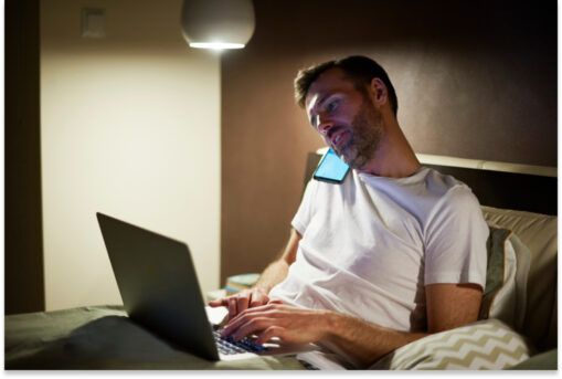 Man on phone at night in bed photo 1