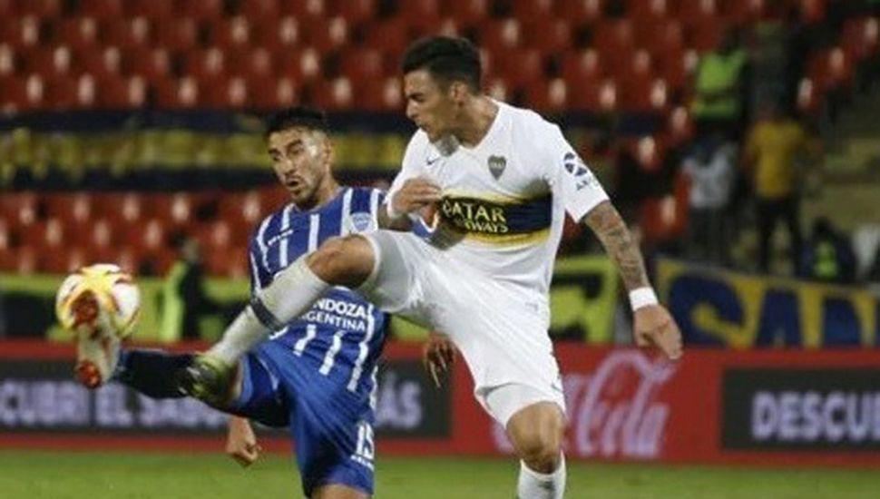 Cristian Pavón, autor del primer gol del triunfo de Boca en Mendoza, lucha por el balón con un zaguero de Godoy Cruz.
