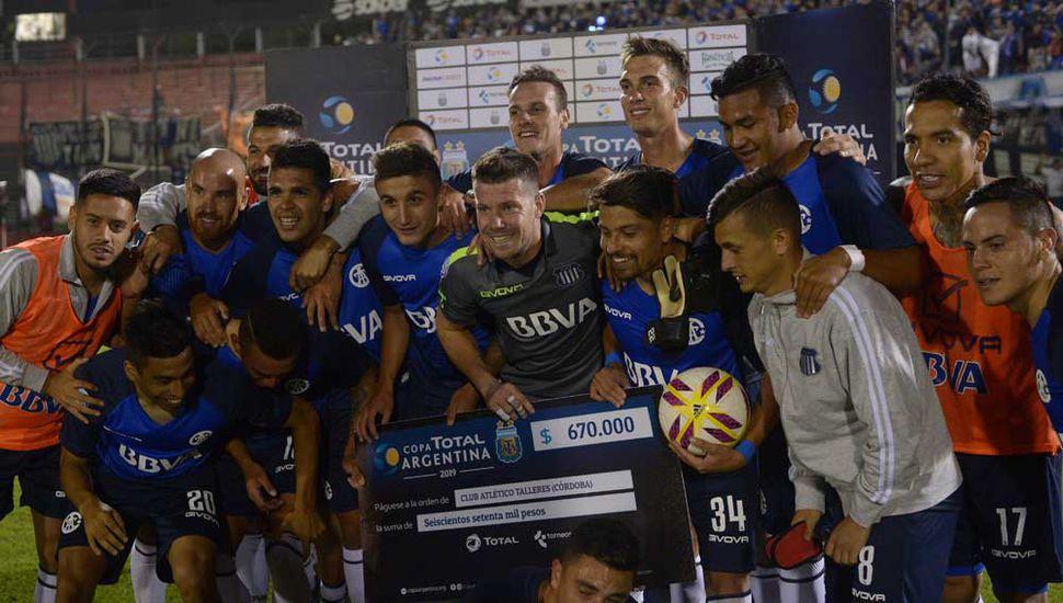 Los jugadores de Talleres de Córdoba festejan con el cheque de 670.000 pesos que obtuvieron como premio.