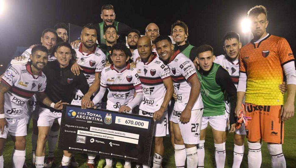 Los jugadores de Colón festejan con el cheque simbólico de 670.000 pesos, obtenido al vencer a Acasusso.