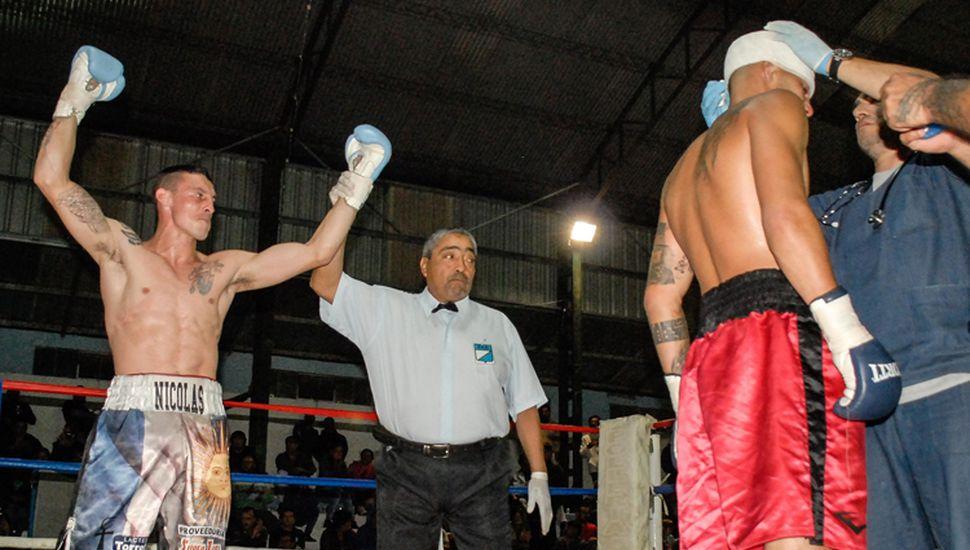 El árbitro Oscar Farías levanta el brazo de Nicolás De León, declarándolo ganador de la pelea de fondo de la velada realizada en Club Rivadavia.
