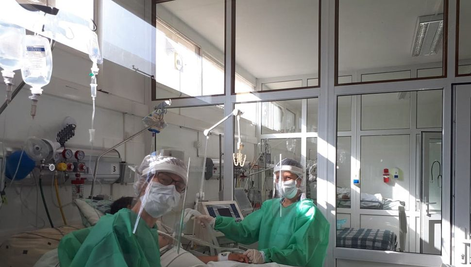 Kinesiólogos junto a pacientes entubados a respirador.