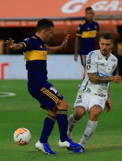 Carlos Tevez lucha por el balón con un jugador del Santos, durante el empate sin goles de anoche, en