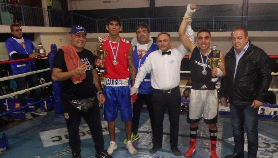 """El ganador, Gastón Colnago (derecha) y el juninense Francisco """"la Cobra"""" Olguín junto a sus técnicos, al árbitro de la pelea y al promotor Marcelo  Crücce."""