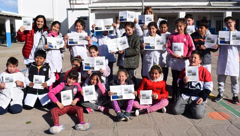 Alumnos y personal de la Escuela N° 1 posan felices con el primer número de la revista que editan.