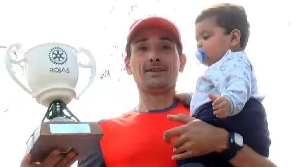 """Junto a su hijito, posa en el podio el ganador de la prueba pedestre disputada en Rojas, el juninense Oscar """"Teté"""" Cabral."""