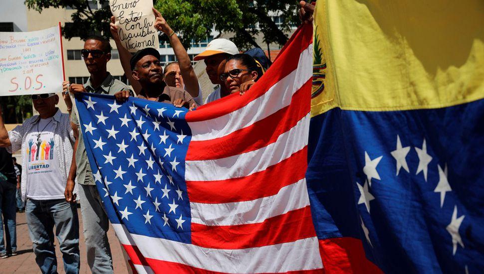 Opositores se manifiestan en Caracas, con banderas de Venezuela y de Estados Unidos.