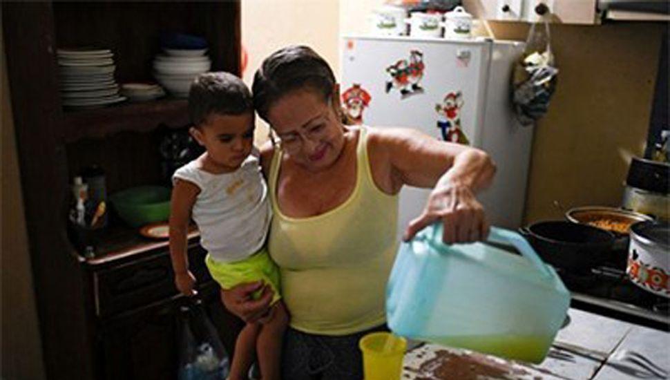 Minu Vásquez sirve un vaso de jugo a uno de sus nietos.