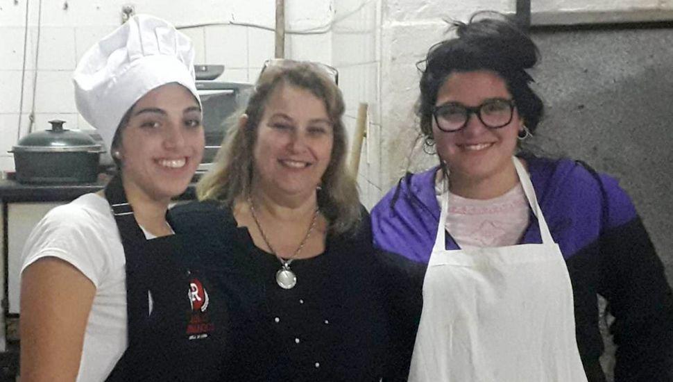Sol Parra y Delfina Larrayoz, cocineras clasificadas en plato principal y postres juveniles, junto a la profesora Viviana Penini.