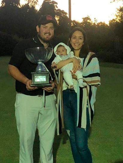 Clarke con un trofeo ganado, posa con su pareja y su hijita.