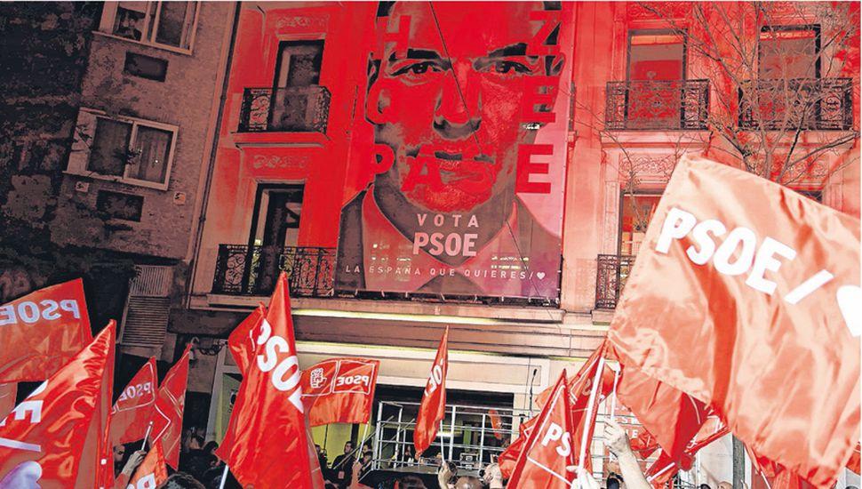 Simpatizantes del psoe, actualmente en el gobierno, celebran frente a la sede partidaria en Madrid.