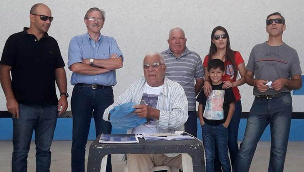 """El presidente Nicolás Milas (izquierda), Abel Oscar """"Cachila"""" Zambrini (sentado) y otros dirigentes de Sarmiento entregando premios de un sorteo."""