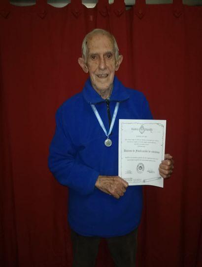 Antonio, feliz, con su diploma y medalla.