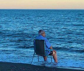 La historia detrás de la foto viral del anciano que llora sentado frente al mar