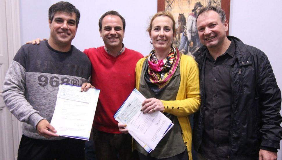 """Omar Castronuovo (izquierda) y Lucrecia Valenza al recibir los aportes municipales, que entregó """"Fredy"""" Zavatarelli, acompañado por el presidente del Consejo Escolar, Gabriel López (derecha)."""