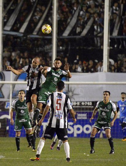 Arriba Sarmiento. Miracco pelea el  balón en lo alto, el delantero del Verde volvió a convertir en un partido clave.